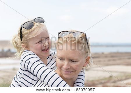 Mom And Daughter Piggy Back Riding Fun Outdoors