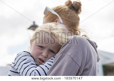 Little Girl Leans Head On Young Lady's Shoulder Outdoors
