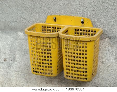 COLOR PHOTO OF PLASTIC BASKET SCREWED ON CONCRETE WALL