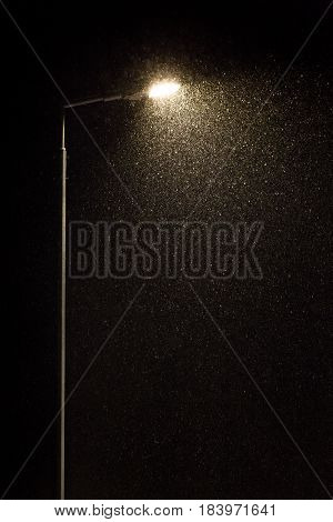 Street lamp and falling snow on a black background. Vertical shot.
