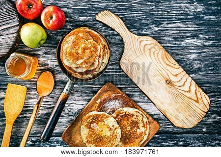 Apple pancakes with cinnamon and honey on textured wood boards. Rustic wooden cutting board. Top view