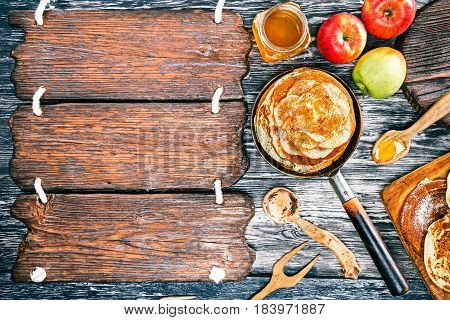 Apple pancakes with cinnamon and honey on textured wood boards. Rustic wooden signboard as frame for your text. Top view