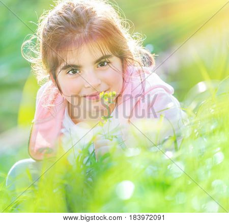 Portrait of a cute baby girl enjoying flowers aroma, having fun on fresh green grass field in spring sunny day, little child with pleasure spending time outdoors