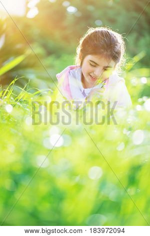 Dreamy photo of a nice little arabic girl on the fresh green grass field, cute child enjoying spring nature, with pleasure spending time outdoors