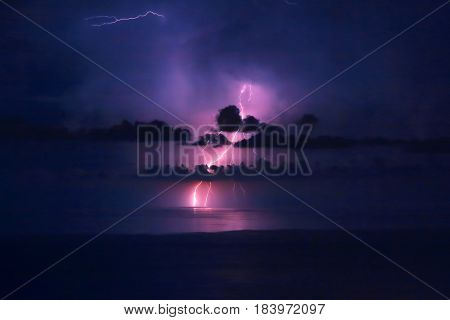 Beautiful dramatic landscape, bright pink lightning over water, storm in the sea, autumn weather, amazing natural wallpaper
