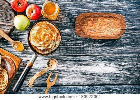 Apple pancakes with cinnamon and honey on textured wood boards. Rustic wooden plate as frame for your text. Top view