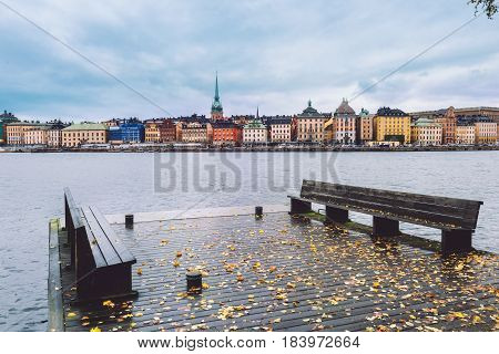 Wide angle view of Stockholm Old Town and Saltsjon bay from Skeppsholm island sea pier. Autumn Stockholm skyline with Gamla Stan, Old German Church and wooden jetty on Skeppsholmen.