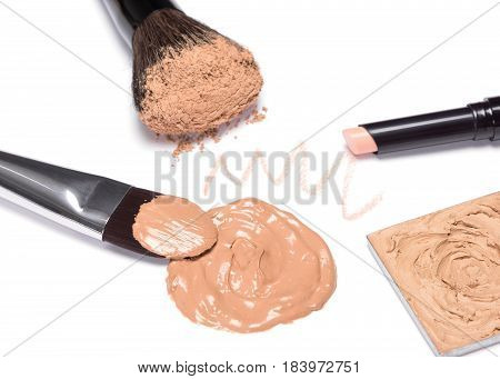 Makeup products to create beautiful skin tone and complexion. Foundation, concealer stick, powder with brushes on white background