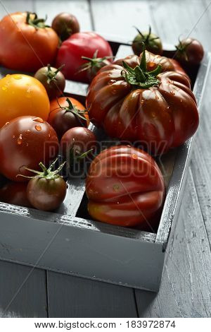 Various colorful organic tomatoes in a box, top view