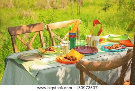 Table served with disposable tableware in garden