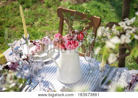 Jug with blooming bouquet of flowers on served table in garden
