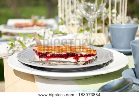 Plate with delicious pie and fork on served table