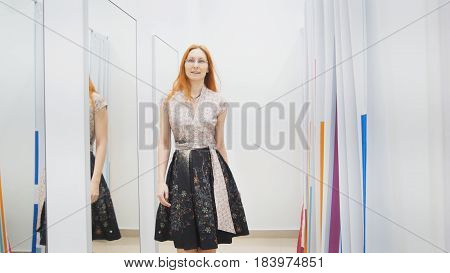 Female trying dress in fitting room - fashion shopping , middle shot