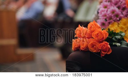 Audience in the concert hall holding flowers and applauding the performance on stage, telephoto