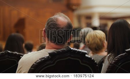 Spectators are watching theatrical performance - bald man, telephoto