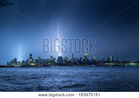 Lightning striking New York City skyscrapers at night. Stormy skies over Midtown West Manhattan from the Hudson River