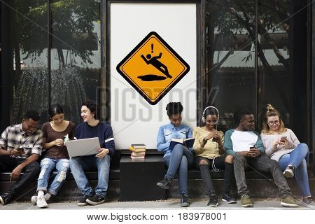 Group of Friends Sitting Together with Slip Caution Attention Banner Behind