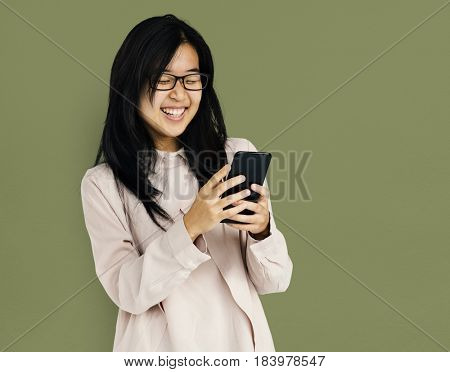 Young adult asian girl smiling and using mobile phone