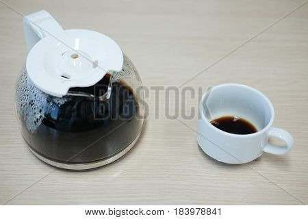 coffee maker and a coffee cup on wood table