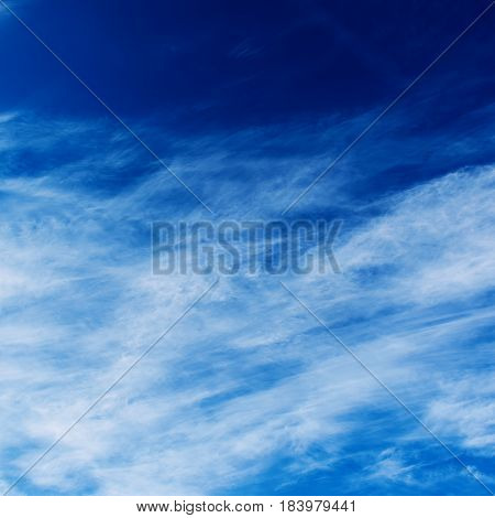 Blue sky with the fluffy white clouds, vivid natural background with copy space
