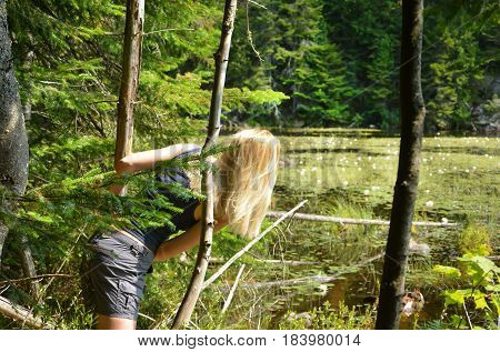 Blond girl in a coniferous forest looking at the lake with water lilies