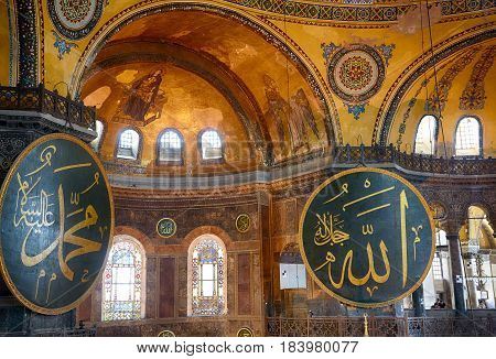 ISTANBUL TURKEY - JULY 9 2014: The interior view of the Hagia Sophia with 2 gigantic circular-framed medallions with the names of Muhammad and Allah and Christian Mosaic image of the Virgin and Archangel Gabriel in the apse on the top of the main dome Ist