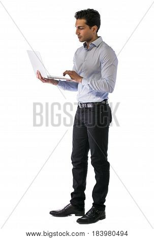 Young attractive man working with computer while standing, isolated on white background. Full length figure