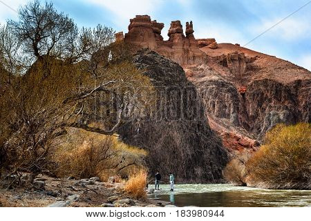 Charyn canyon, Almaty region, Kazakhstan - April 15, 2017. Tourists on the mountain river against the background of red rocks. Charyn National Park - a unique object of nature, where the shape of the relief took shape of isolated rocks, columns and towers
