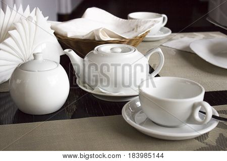 White tea set on the table in the restaurant