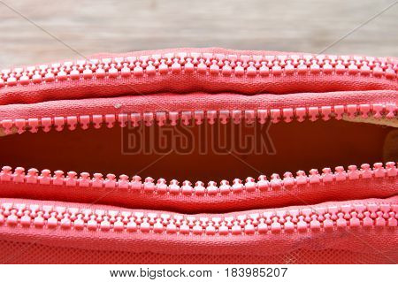 red fabric purse zipper slide opened on wooden board