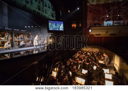 MOSCOW - JAN 25, 2017: Shooting camera, prisoners on stage and orchestra pit at Passenger performance in Moscow Theater New Opera, focus on camera