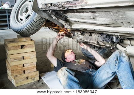 A worker is repairing an old car. Bottom view.