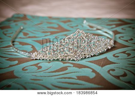Silver sparkly bridal or prom tiara on turquoise with brown background