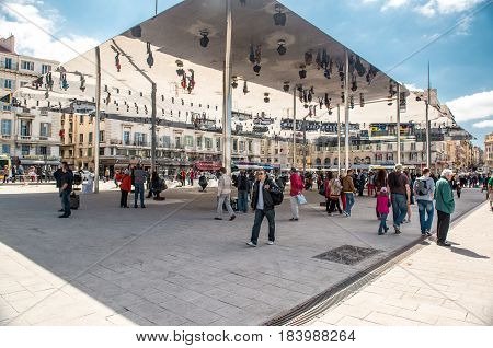 Marseille France - May 3 2013: Crowd of people walk under reflecting awning at Vieux-Port of Marseille. The Vieux-Port of Marseille is the largest urban harbour in Europe. France