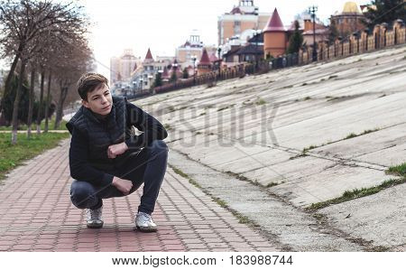 Stylish young man sitting near a fence on the waterfront