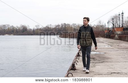 Happy teenager walking along the city embankment