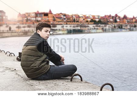 Stylish young man sitting near a Rivers on the waterfront