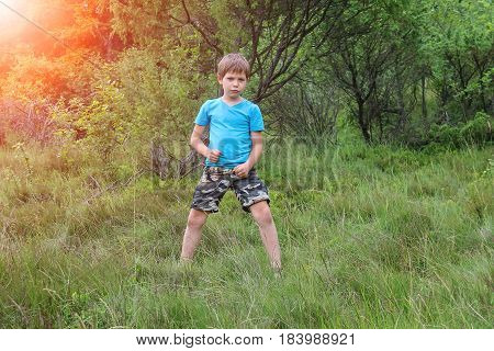 Boy stands among trees in forest park in sunlight