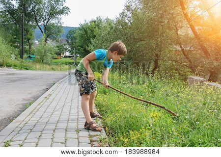 Boy playing with wooden stick on roadside in sunlight