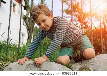 Small boy in striped sweater and shorts on big rocks in sunlight