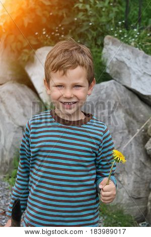 Smiling boy with dandelion in front of big rocks in sunlight