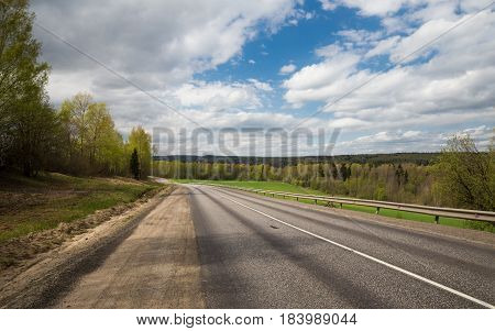 A Deserted country road along the forest under blue sky with clouds
