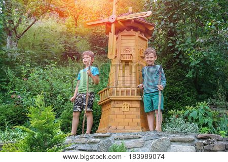 Two boys next to small mill in summer city park in sunlight