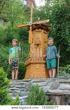Two boys next to small mill in summer city park