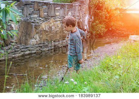 Small boy near narrow creek in city park
