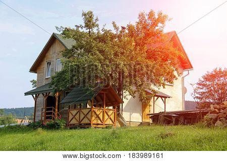Modern cottage with porch and veranda in sunlight. Carpathians Ukraine