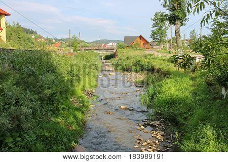 Narrow creek in small town of Carpathians Ukraine