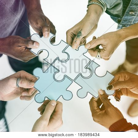 Human hands holding jigsaw together