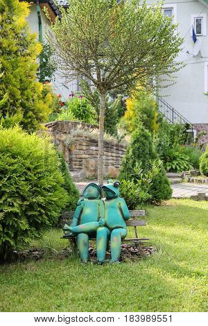 Schodnica Ukraine - June 30 2014: Decorative funny frogs sitting on bench in city park