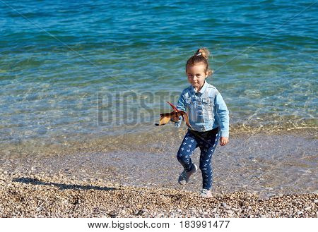 Little adorable girl with a pterodactyl dinosaur toy on the beach